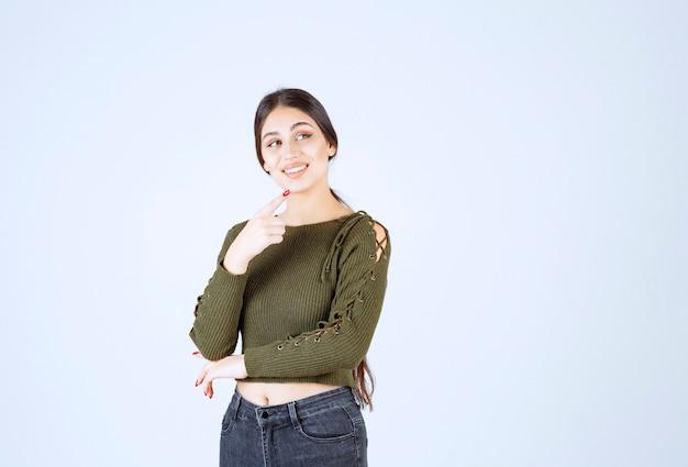 Jolie jeune femme pointant à ses côtés sur un mur blanc
