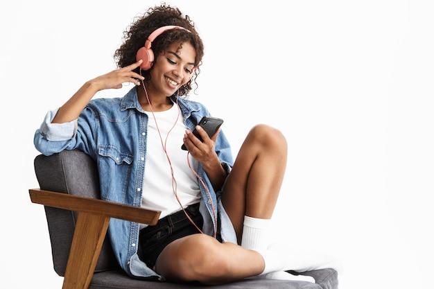 Jolie jeune femme portant du denim assis sur une chaise isolée sur un mur blanc, écoutant de la musique avec des écouteurs, utilisant un téléphone portable