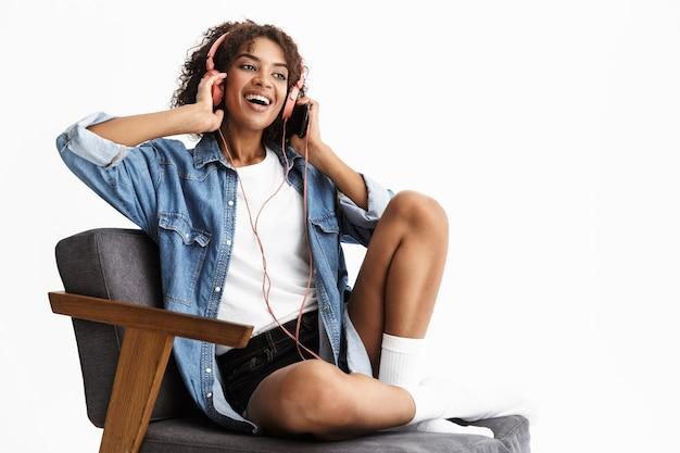 Jolie jeune femme portant du denim assis sur une chaise isolée sur un mur blanc, écoutant de la musique avec des écouteurs
