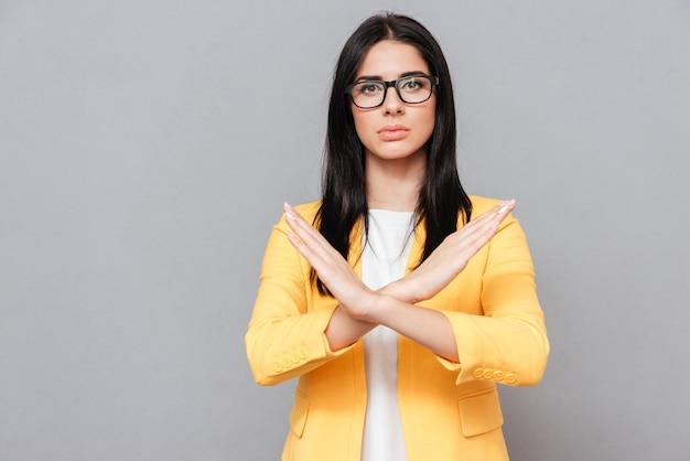 Une jolie jeune femme portant des lunettes et vêtue d'une veste jaune sur une surface grise fait un panneau d'arrêt. regardez devant.