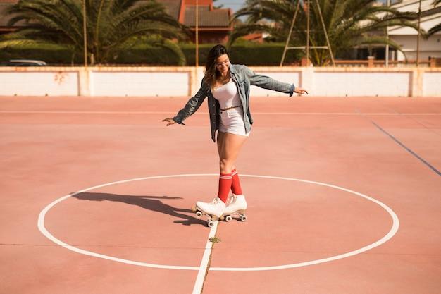 Une jolie jeune femme portant des patins à roulettes patiner sur le court