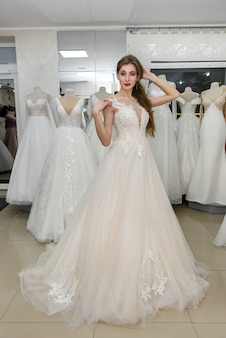 Jolie jeune femme portant une robe de mariée en boutique de mariée