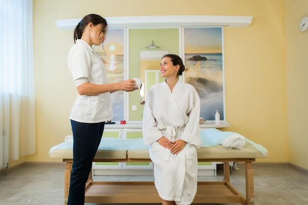 Jolie jeune femme portant une robe et une masseuse parlant après le massage dans un spa en buvant du thé