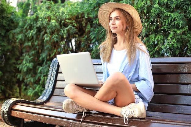 Jolie jeune femme portant des vêtements d'été travaillant sur ordinateur portable alors qu'elle était assise sur un banc dans la rue de la ville.