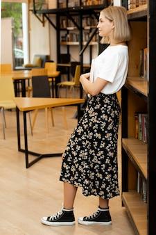 Jolie jeune femme posant à la bibliothèque