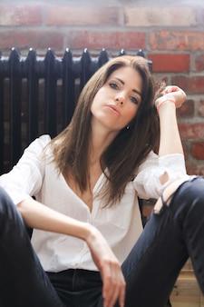 Jolie jeune femme posant dans une chemise blanche et un jean