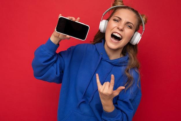 Jolie jeune femme positive émotionnelle portant un sweat à capuche bleu élégant isolé sur fond rouge