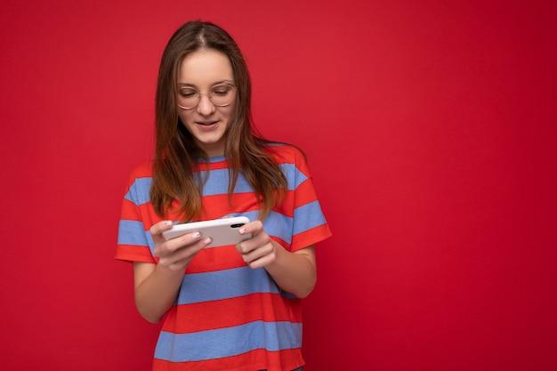 Jolie jeune femme positive et séduisante portant des lunettes optiques et une tenue élégante décontractée isolée sur fond avec un espace vide tenant dans la main et utilisant la messagerie de téléphone portable sms look