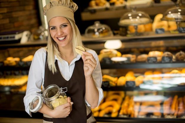 Jolie jeune femme avec un pot à biscuits dans la boulangerie