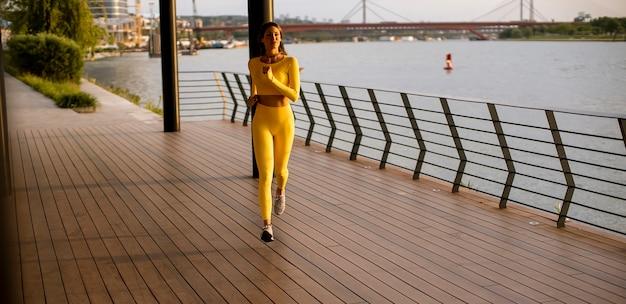 Jolie jeune femme prenant l'exercice de course par la promenade de la rivière