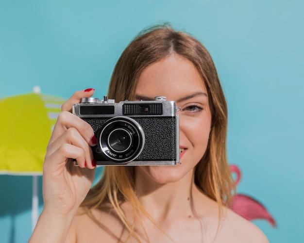 Jolie jeune femme prenant une photo à la chambre