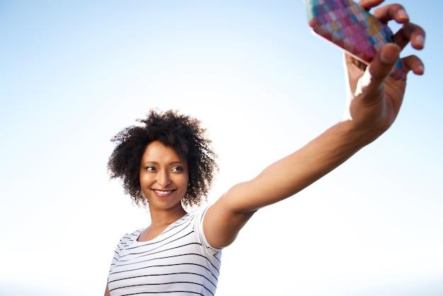 Jolie jeune femme prenant selfie avec un téléphone cellulaire à l'extérieur