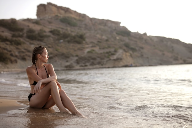 Jolie jeune femme profitant de la belle vue sur la mer paisible sur la plage pendant la journée