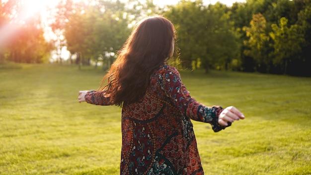 Jolie jeune femme profitant de son temps à l'extérieur dans le parc - heure d'été