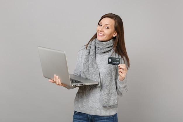 Jolie jeune femme en pull gris, écharpe travaillant sur ordinateur portable, tenant une carte bancaire de crédit isolée sur fond de mur gris. mode de vie sain, conseil en traitement en ligne, concept de saison froide.