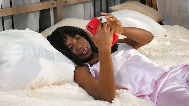 Jolie jeune femme en pyjama se trouve dans son lit prend un smartphone