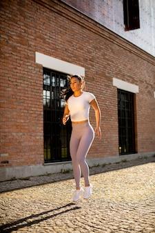 Jolie jeune femme qui court dans la rue