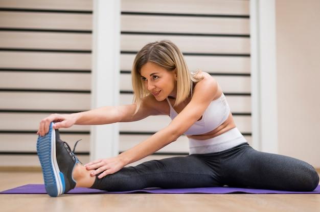 Jolie jeune femme qui s'étend à la gym