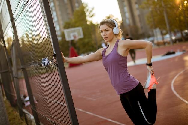 Jolie jeune femme qui s'étend pendant un entraînement sportif