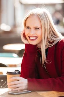 Jolie jeune femme de race blanche assis dans un café à l'extérieur de boire du café