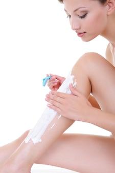 Jolie jeune femme à raser les jambes avec un rasoir isolé sur blanc