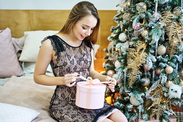 Jolie jeune femme recevant des cadeaux de noël contre l'arbre de noël.