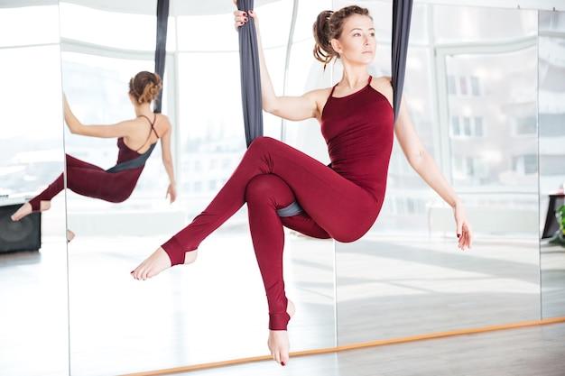 Jolie jeune femme réfléchie faisant une pose de yoga aérien à l'aide d'un hamac