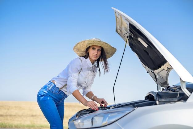 Jolie jeune femme regardant le moteur de la voiture cassée. problèmes de route.