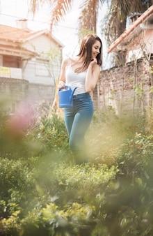 Une jolie jeune femme regardant des plantes vertes dans la serre