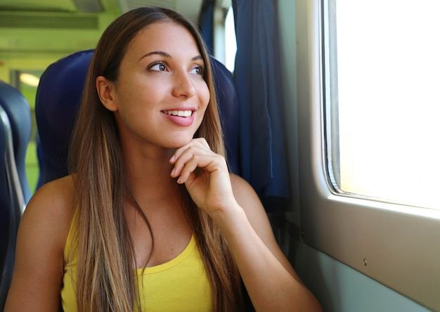 Jolie jeune femme regardant à travers la fenêtre du train ou du bus. passager de train heureux voyageant assis sur un siège et regardant par la fenêtre.