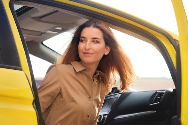 Jolie jeune femme regarde sur le côté tout en sortant de sa voiture jaune. beaux rayons de soleil sur le pare-brise