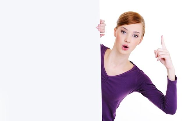 Jolie jeune femme regarde du panneau d'affichage vide avec l'index de l'ascenseur vers le haut. concept d'idée