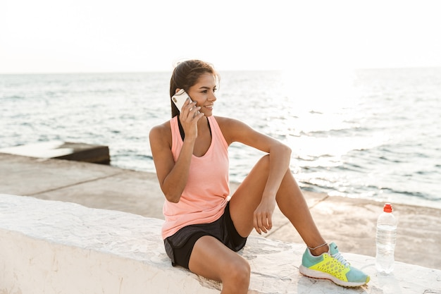 Jolie jeune femme de remise en forme à l'aide de téléphone portable tout en se reposant sur la plage après le jogging, parler