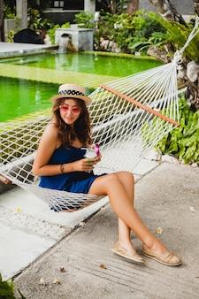 Jolie jeune femme en robe bleue et chapeau de paille portant des lunettes de soleil roses, boire un cocktail d'alcool en vacances assis dans un hamac en tenue de style estivale