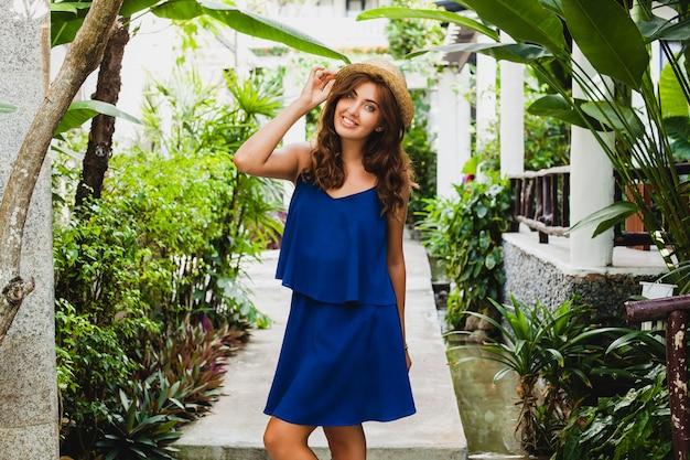 Jolie jeune femme en robe bleue et chapeau de paille