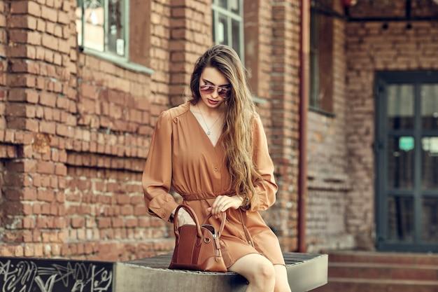 Jolie jeune femme en robe courte assise sur le banc et à la recherche de quelque chose dans le sac
