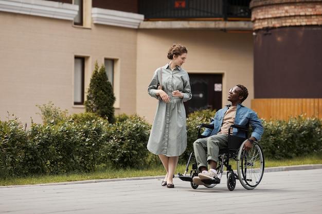 Jolie jeune femme en robe marchant le long de la rue et parlant à un homme handicapé tout en sortant avec lui