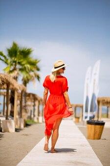Jolie jeune femme en robe rouge marchant sur une plage en été