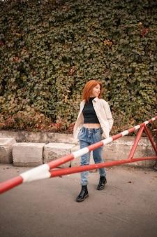 Une jolie jeune femme rousse marche dans la rue, elle est vêtue d'un jean et d'une chemise beige. belle fille habillée dans un style décontracté avec un sourire sur son visage