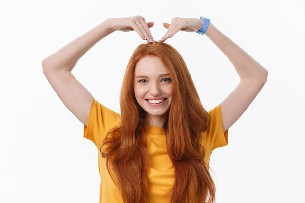 Jolie jeune femme rousse romantique faisant un geste de coeur avec un sourire tendre heureux