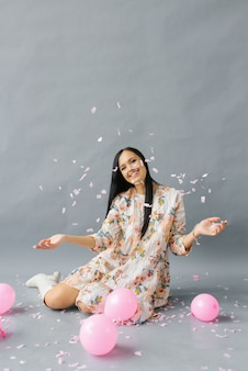 Une jolie jeune femme s'assoit près des ballons roses et jette des confettis et des sourires et sur un fond gris