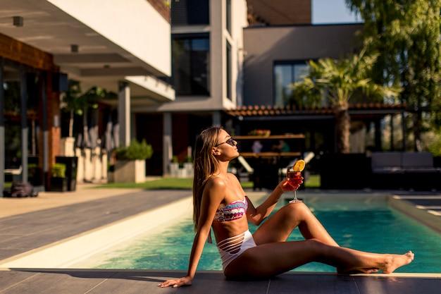 Jolie jeune femme se détendre au bord de la piscine