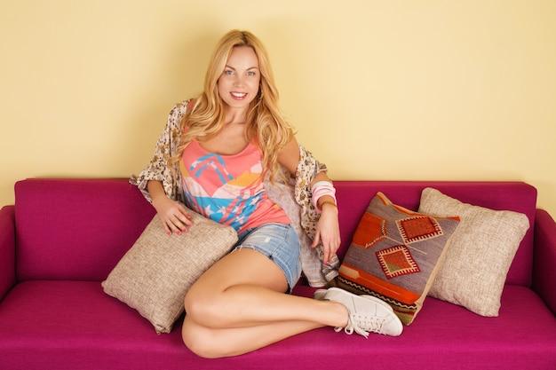 Jolie jeune femme se détendre sur un canapé à la maison