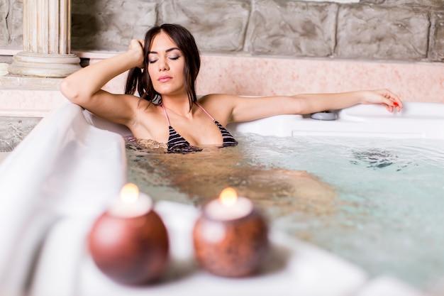 Jolie jeune femme se détendre dans le bain à remous