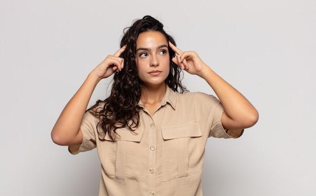 Jolie jeune femme se sentant confuse ou doutant, se concentrant sur une idée