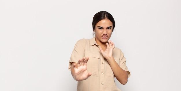 Jolie jeune femme se sentant dégoûtée et nauséeuse, s'éloignant de quelque chose de méchant, malodorant ou puant, disant beurk
