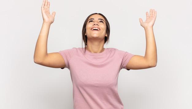 Jolie jeune femme se sentant heureuse, étonnée, chanceuse et surprise, célébrant la victoire avec les deux mains en l'air
