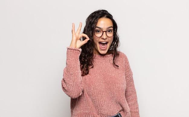 Jolie jeune femme se sentant réussie et satisfaite, souriant avec la bouche grande ouverte, faisant signe correct avec la main