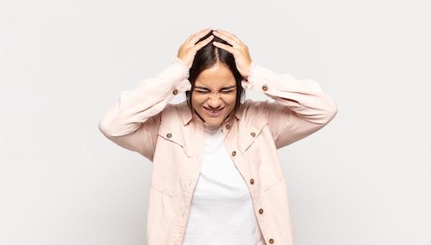 Jolie jeune femme se sentant stressée et frustrée, levant les mains à la tête, se sentant fatiguée, malheureuse et souffrant de migraine
