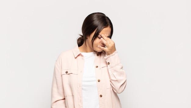 Jolie jeune femme se sentant stressée, malheureuse et frustrée, touchant le front et souffrant de migraine de maux de tête sévères